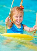 Cute happy baby girl enjoying summer holiday in the pool, having fun on water swing, red frangipani