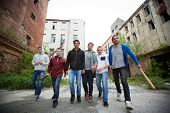 stock photo of mobsters  - Portrait of spiteful hooligans walking down street - JPG
