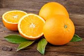 stock photo of orange  - Oranges Fruit with leaves over Wooden background - JPG