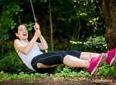 foto of seesaw  - Young woman swinging on seesaw outdoor in nature - JPG