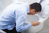 image of vomit  - Young man drunk or sick vomiting in toilet at home - JPG