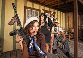 stock photo of tommy-gun  - Tough gangster woman with cigar and submachine gun - JPG