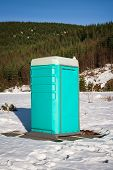 pic of porta-potties  - Portable bathroom in a snow filled parking lot - JPG