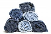 picture of denim jeans  - Rolled blue denim jeans arranged in stack - JPG