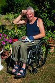 foto of circumcision  - Retired person in a wheelchair starts to sweat during gardening - JPG