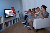 picture of realism  - Conceptual image of a family watching 3D television and stretching out their hands as though to touch the image on the screen - JPG