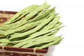 picture of mange-toute  - Snow peas in wicker basket isolated on white