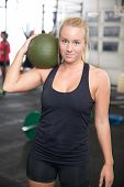 stock photo of slam  - Attractive young girl rests with a slam ball on the shoulder after workout at a fitness gym center - JPG