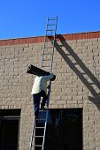 stock photo of osha  - A roofing company worker climbs a high ladder to the top of a building holding a heavy roll of tarpaper - JPG