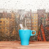 stock photo of rainy day  - Steaming coffee cup on a rainy day window background - JPG