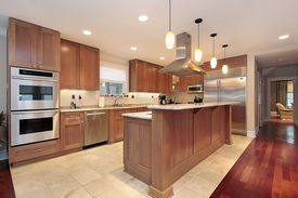 stock photo of light fixture  - Kitchen in luxury home with oak wood cabinetry - JPG