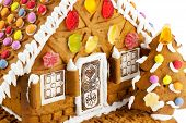 image of gingerbread house  - Close up of colorful gingerbread house isolated against white background - JPG