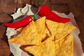 image of nachos  - Tasty nachos and chili pepper on paper - JPG