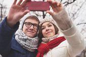picture of amor  - Amorous dates in winterwear taking selfie outdoors  - JPG