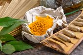 stock photo of curcuma  - Tumeric powder spice on wooden board with tabletes as healthy supplement of diet - JPG