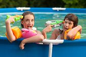 foto of friendship belt  - Two teenage girls having fun with their childhood toys in the home pool - JPG