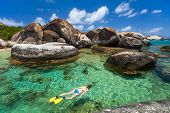 foto of virginity  - Young woman snorkeling in turquoise tropical water among huge granite boulders at The Baths beach area major tourist attraction on Virgin Gorda - JPG