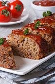 picture of meatloaf  - Meatloaf with ketchup closeup sliced on a white plate vertical - JPG