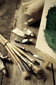 pic of knife  - Artistic paintbrushes tubes of oil paint palette knife and easel with oil painting on old wooden desk - JPG