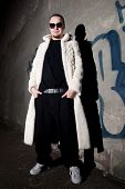 picture of hustler  - Man in long white fur coat posing like a pimp near the grungy 