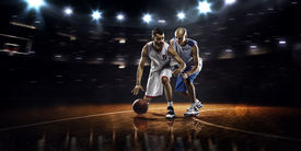 stock photo of slam  - Two basketball players in action in gym in lights - JPG