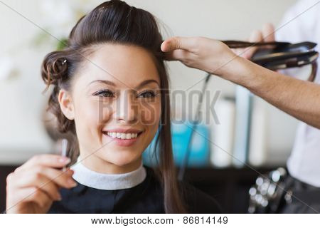 poster of beauty, hairstyle and people concept - happy young woman and hairdresser with hair iron making haird