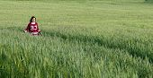 image of wheat-free  - Young happy caucasian teenage girl dressed in red and walking free on a green wheat field late in spring - JPG