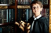 stock photo of school carnival  - A boy stands in the library by the bookshelves with many old books and holds old manuscripts - JPG