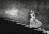 picture of step-up  - Young woman in white long dress stepping up the staircase - JPG