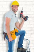 image of handyman  - Confident handyman holding power drill while climbing ladder against white wall - JPG