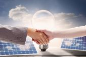 pic of light fixture  - Handshake between two women against light bulb and solar panels on floorboards in the sky - JPG