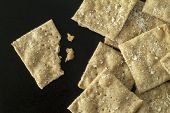 foto of whole-grain  - Freshly baked whole wheat crackers with salt grains on a black iron surface - JPG