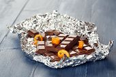 stock photo of orange peel  - Chocolate with orange peels in foil on wooden background - JPG