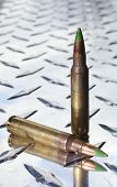 picture of cartridge  - Cartridges with green tipped bullets on chrome armor plate aluminum - JPG