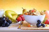 image of fruit bowl  - Bowl of cereal with fruit on a white wooden table and fresh fruits behind front view - JPG