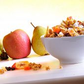 picture of fruit bowl  - Bowl of cereal with fruit on a white wooden table and fresh fruits behind - JPG
