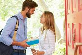 stock photo of say goodbye  - Woman Saying Goodbye To Man Leaving Home With Packed Lunch - JPG