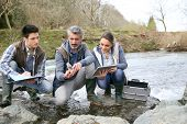 picture of water pollution  - Biologist with students in science testing river water - JPG