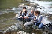 image of water pollution  - Biologist with students in science testing river water - JPG