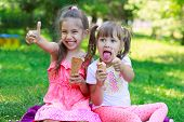 image of healthy eating girl  - Girls kids sisters friends teasing showing off tongues sitting on grass eating ice cream thumb up focus on younger girl - JPG