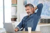 stock photo of senior class  - Mature man relaxing in front of laptop in class - JPG