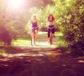 stock photo of bike path  - two girls riding bikes on a path in a park full of trees toned with a retro vintage instagram filter effect app or action  - JPG