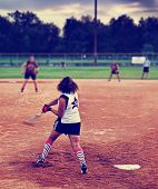 foto of softball  -  a young girl batting a ball at home plate in a softball game toned with a retro vintage instagram filter  - JPG