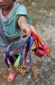 stock photo of hmong  - Young unrecognized person selling homemade colorful bracelets to tourist to make her living and help her family - JPG