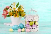 image of caged  - Easter composition with Easter eggs in decorative cage and flowers - JPG