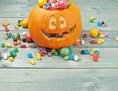 stock photo of jacking  - Jack o lantern halloween pumpkin filled with multiple colorful sweets and candies over the wooden board background composition - JPG