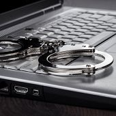 stock photo of handcuff  - handcuffs on the laptop cyber crime concept - JPG