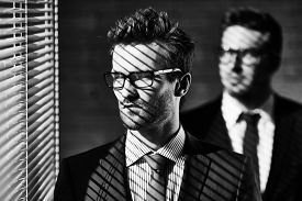 stock photo of jalousie  - Elegant young businessman in eyeglasses looking through jalousie on background of colleague - JPG