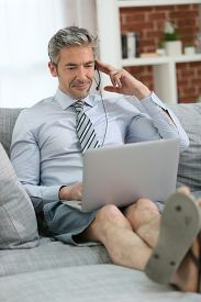 picture of stressless  - Businessman with headset working from home on couch - JPG