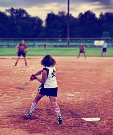 image of softball  -  a young girl batting a ball at home plate in a softball game toned with a retro vintage instagram filter  - JPG